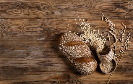 avena en hojuelas: Vista superior de pan con los copos de avena y floretes de avena en el fondo de madera vieja con el espacio.