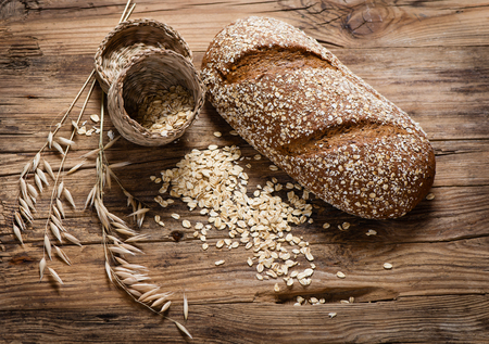 flakes: Oat whole grain bread, rolled oats and oat plants on rustic wooden background.