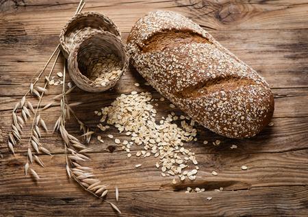 avena en hojuelas: toda la avena pan integral, copos de avena y plantas de avena en el fondo de madera rústica. Foto de archivo
