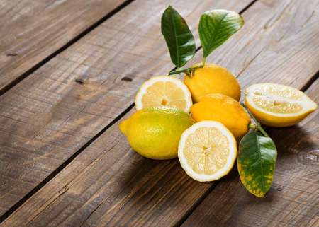 Wholes and halved lemon with leaves on old wooden background