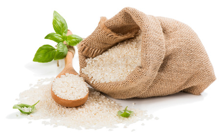white rice: Raw grain white rice grains in burlap bag decorated with green basil isolated on white background.