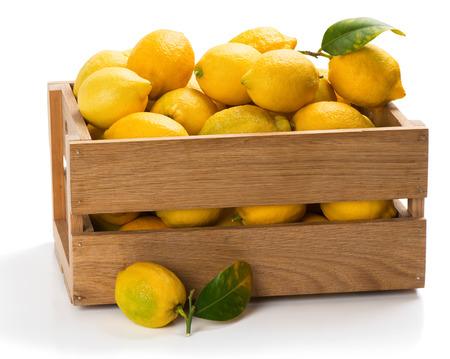 limon: Limones con hojas verdes en una caja con una en la superficie en el primer plano aislado en el fondo blanco.