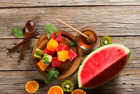 hojas antiguas: Top view of colorful fruit salad (watermelon, kiwi, orange) with mint leaves on old wooden table. Foto de archivo