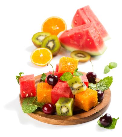 ensalada de frutas: Ensalada de frutas de verano (sandía, kiwi, naranja, cereza, menta) con ingredientes hojas en un plato de madera aislado en un fondo blanco.