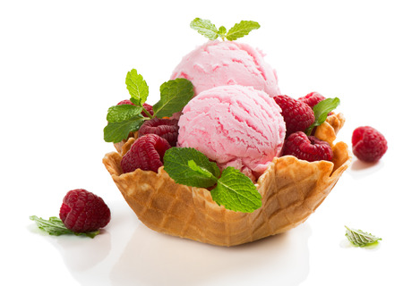 Berry sorbet and fresh raspberries in a wafer bowl isolated on black background