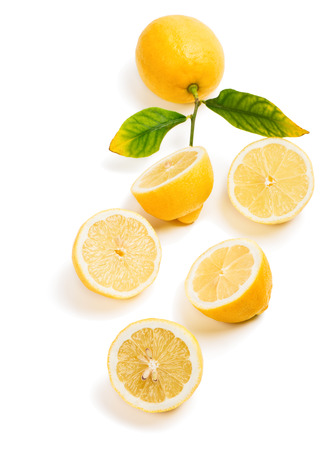 Top view of fresh lemons whole with green leaves and halves isolated on a white background.