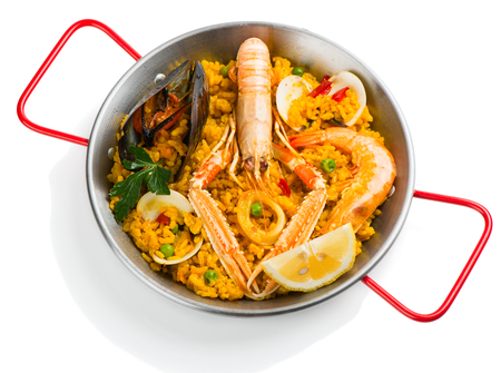 langoustine: Paella with langoustine, mussel, prawn and vegetables in a small paellera isolated on a white background.