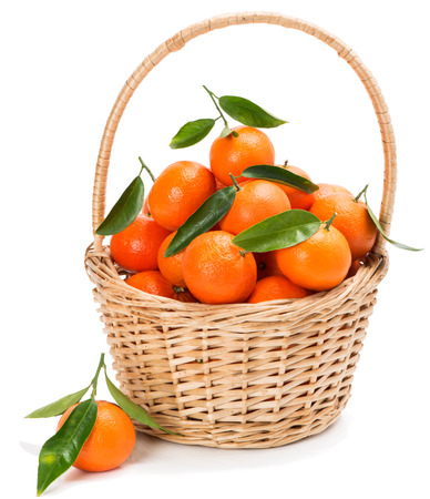ripe: Tangerine or clementine fruit with green leaves in a basket isolated white background.