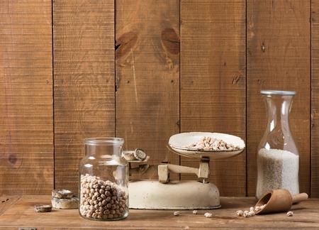 vintage kitchen: Vintage kitchen scale weighing chickpea on wooden background.