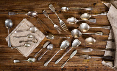 fork and knife: Top view of collection of  antique kitchen utensils ( spoon, fork,  teaspoon, knife, tea-strainer) on a old wooden background. Stock Photo