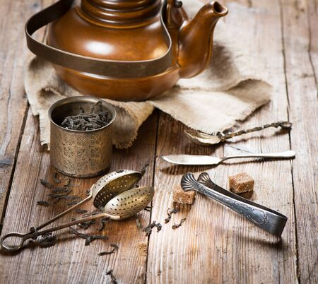 Dry black tea, brown clay kettle, tea strainer, sugar on a old wooden background.