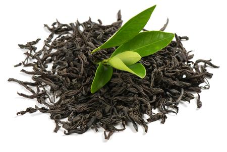 Tas de thé sec avec des feuilles vertes isolées sur fond blanc.