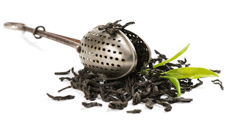 infuser: Dry black tea and fresh tea leaves and a vintage tea strainer isolated on white background. Stock Photo