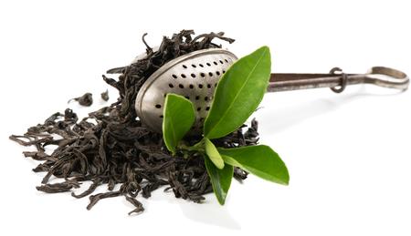 infuser: Dry black tea, vintage tea strainer and fresh tea leaves, isolated on white background.