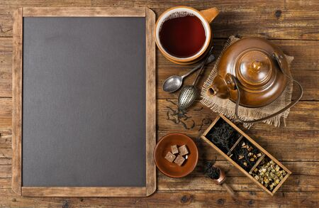 tea table: Top view of teapot and cup with drink and black chalkboard for menu with copy space for your text. Stock Photo