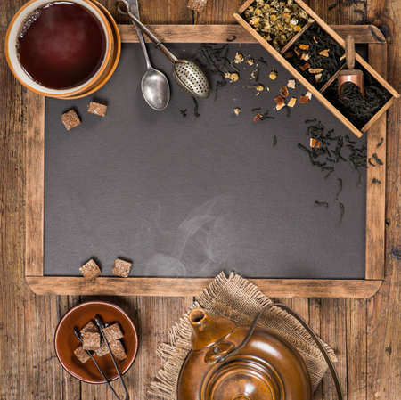 infuser: Tea concept - a hot, steaming cup of tea with a teapot, on a wooden background and blackboard with copy space for menu.