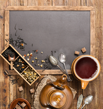 Top view of assortment of fragrant dried teas and Cup of tea with teapot on a blackboard with copy space for your text. Stock Photo
