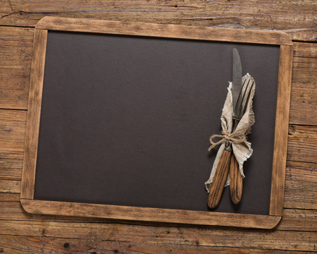 string top: Top view of vintage fork and spoon tied with string on linen napkinon a blackboard on a old wooden table with copy space.
