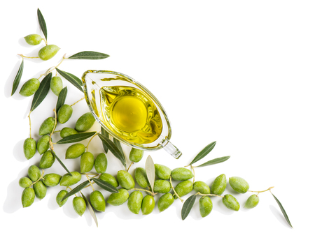 Top view of angular frame of green fresh olives with leaves and olive oil in a glass sauce boat isolated on white background.