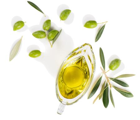 Bovenaanzicht van sausboot met olijfolie en verse groene olijven geïsoleerd op witte achtergrond.