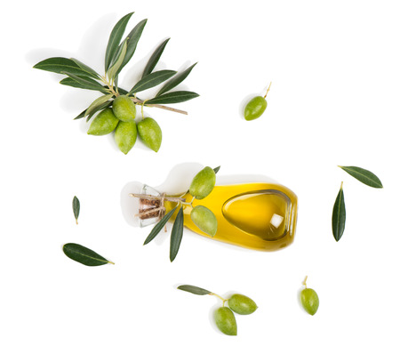 Top view of branch with green olives and a bottle of olive oil isolated on white background.