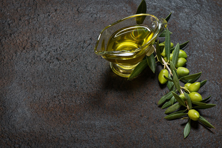 Twig with green olives and glass sauce boat of olive oil on a black old  metal background.