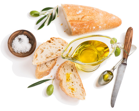 Top view of freshly baked white bread with olive oil and salt decorated with raw olives fruit with green leaves isolated on white background.