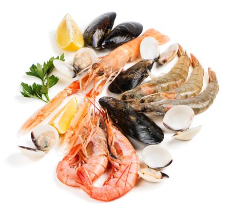 Ongekookte schelpdieren (langoustine, garnalen, schelpdieren, mosselen, clam) versierd met citroen en peterselie op een witte achtergrond. Stockfoto