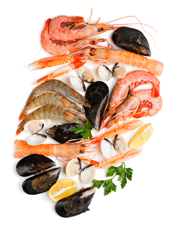 Top view of uncooked seafood (langoustine,  shrimp,  shellfish,  mussel,  clam) decorated with lemon and parsley isolated on white background.