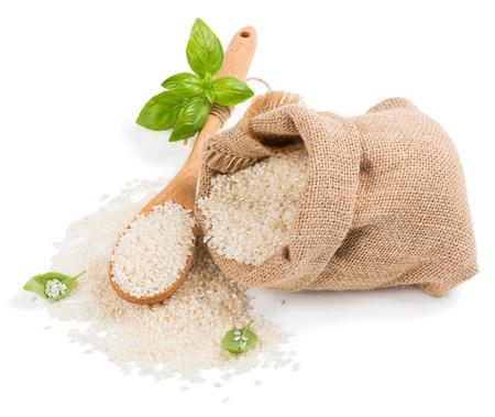 arroz blanco: Arroz blanco redondo salpicado de saco de arpillera con una cuchara de madera aislada sobre un fondo blanco. Foto de archivo