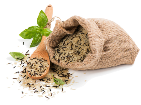 Wild rice sprinkled from burlap sack with wooden spoon isolated on a white background.