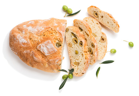 Top view of traditional white bread with olives decorated with raw olives fruit with green leaves isolated on white background.