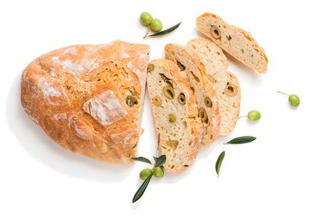 Vista superior de pan blanco tradicional con aceitunas adornados con aceituna cruda de frutas con hojas verdes aisladas sobre fondo blanco. Foto de archivo