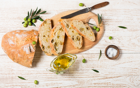 Top view of tasty white bread with olives and olive oil on a rustic wooden background with copy space.