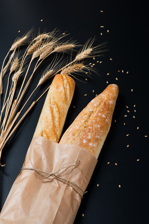 string together: Loaves of french baguette bread tied together with paper and string decorated with wheat ears and cereals on a black background. Stock Photo
