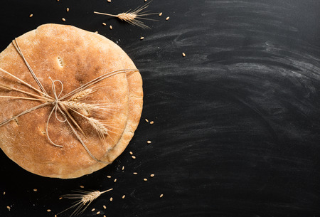 string together: Top view of loaves of pita bread tied together with and string decorated with wheat ears on a floured black background.