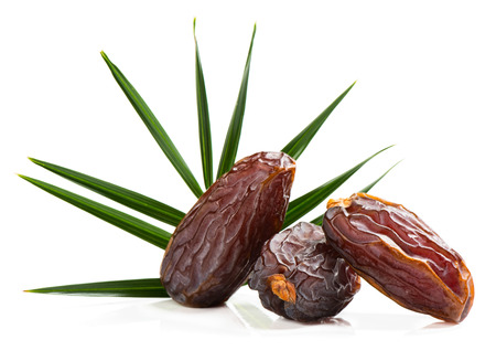 green dates: Close up of three big dates fruit with green leaf of palm tree isolated on white background.