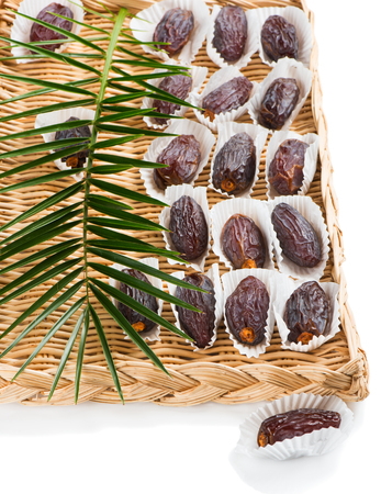 palm fruits: Date fruits (Medjool) with leaf of palm tree in a wicker tray with one on the surface in the foreground, isolated on white background.