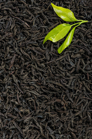 green and black: Top view of black tea background with green leaves. Stock Photo