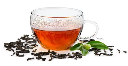 comida inglesa: Copa de vidrio con té, hojas de color verde y el té negro seco aislado en el fondo blanco. Foto de archivo