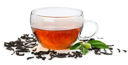 Cup of glass with tea, green leaves and dry black tea isolated on white background.