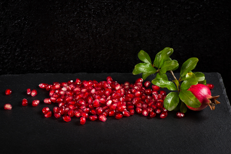 black boards: Loose pomegranate seeds on a black slate board and twig of pomegranate tree with fruit and green leaves.