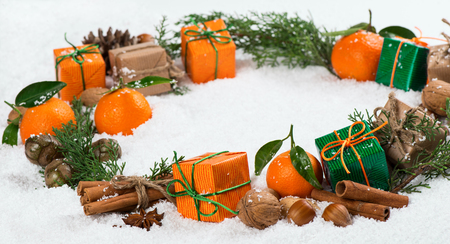 hristmas: ?hristmas wreath made of green branches, pine cones, christmas gifts, tangerine, walnuts, hazelnut and cinnamon sticks on snow.