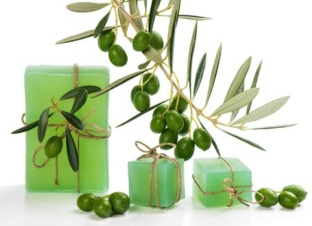 background settings: Olive soap and branch of olive tree with green olive fruits isolated on white background.  Spa concept.