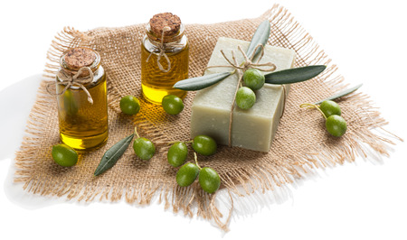 Bottles of aroma essential olive oil, soap and green olives isolated on white background. SPA concept.