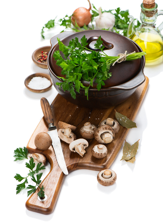 champignon: Cooking pot and uncooked ingredients for mushroom soup (fresh brown champignon mushrooms, olive oil, spices) on a cutting wooden board isolated on white background.