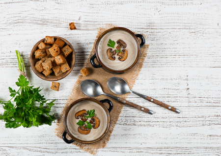 two on top: Top view of two bowls of portions of mushroom cream soup serving with croutons and parsley on a white rustic wooden table with copy space for text.