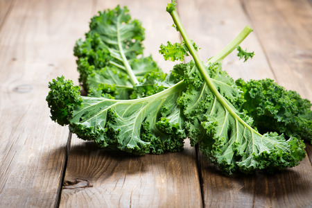 Close up of kale. Green vegetable leaves on a rustic wooden background.