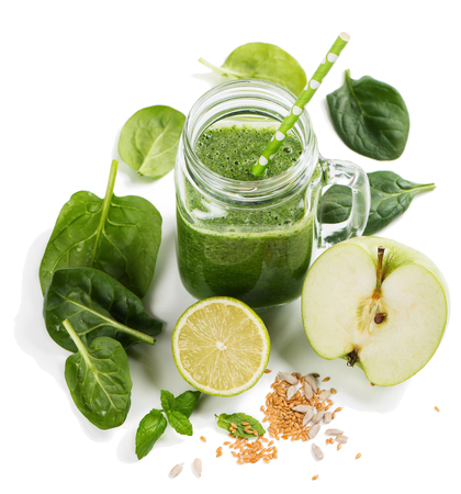 Healthy green smoothie and ingredients on white: spinach, apple, lime and cereals. Isolated on white background.