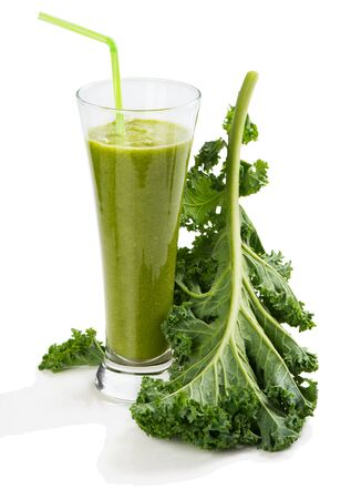 repollo: Green smoothie in a glass and big leaf of kale isolated on white background. Foto de archivo